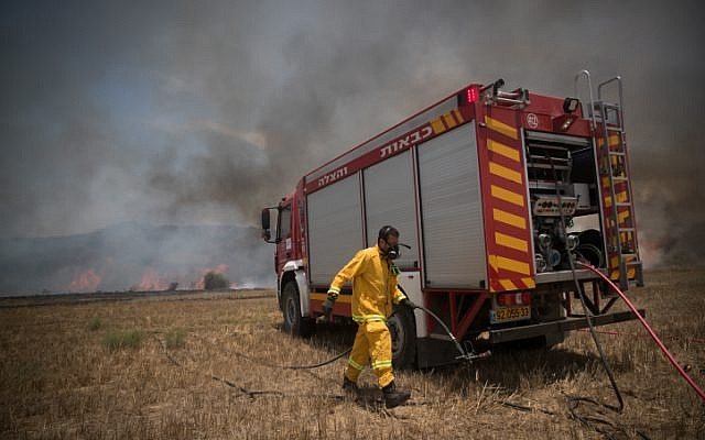 Israeli firefighters extinguish a fire in a field in southern Israel, caused by kites flown by Palestinians from the Gaza Strip on June 5, 2018. (Yonatan Sindel/Flash90)