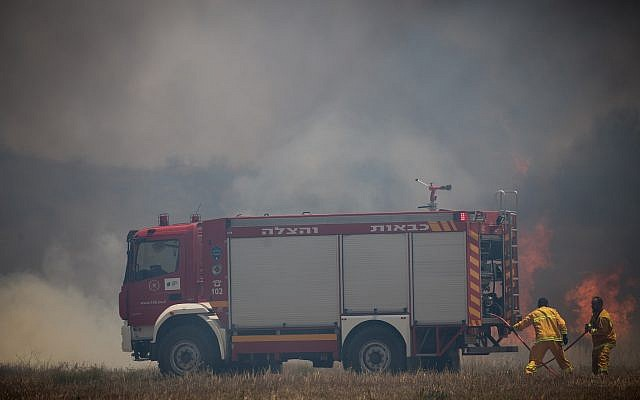 An illustrative photo of Israeli firefighters battling a fire sparked by a flaming object launched from the Gaza Strip, near the border with Palestinian enclave, of June 5, 2018. (Yonatan Sindel/Flash90)