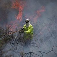 An illustrative photo of a firefighter extinguishing a fire in a field near the Gaza Strip that was sparked by a flaming object flown from the Palestinian enclave, on June 5, 2018. (Yonatan Sindel/Flash90)