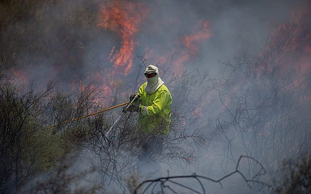 Illustrative. A firefighter extinguishing a fire in a field near the Gaza Strip that was sparked by a flaming object flown from the Palestinian enclave, on June 5, 2018. (Yonatan Sindel/ Flash90)