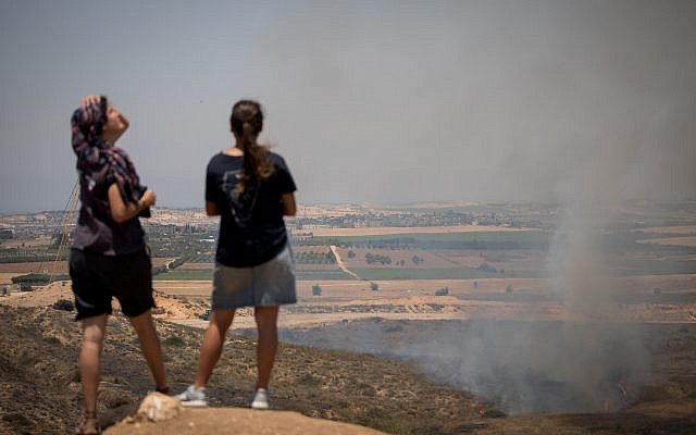 Israeli girls watch a fire caused from kites flown by Palestinians, near the border with the Gaza Strip, June 8, 2018. (Yonatan Sindel/ Flash90)