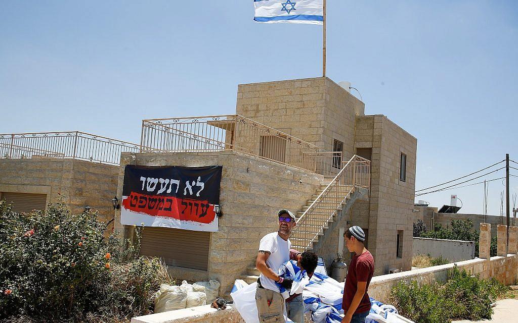 People seen near a home slated for demolition in the illegal Jewish neighborhood of Netiv Ha'avot  on June 11, 2018. (Gershon Elinson/Flash90)