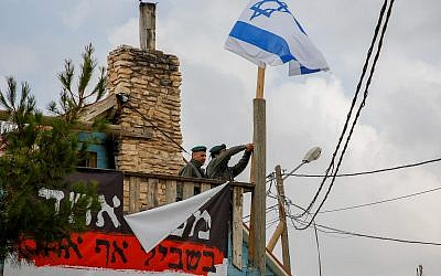 Border Police remove an Israeli flag hanging from a home slated for demolition in the Netiv Ha'avot outpost on June 13, 2018. (Gershon Elinson/Flash90)