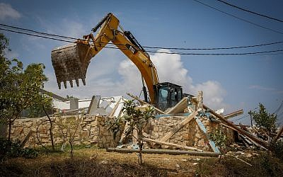A bulldozer demolishes a homes in the Netiv Ha'avot outpost on June 13, 2018. (Gershon Elinson/Flash90)