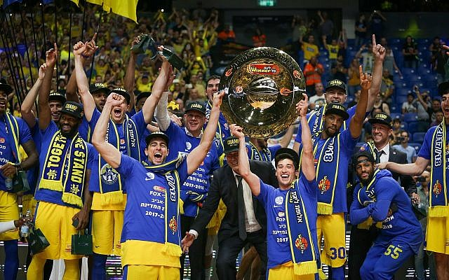 Maccabi Tel Aviv basketball team players raise the championship plate after defeating Hapoel Holon at the final of the Israeli Basketball Premier League in Tel Aviv, June 14, 2018 (Roy Alima/Flash90)