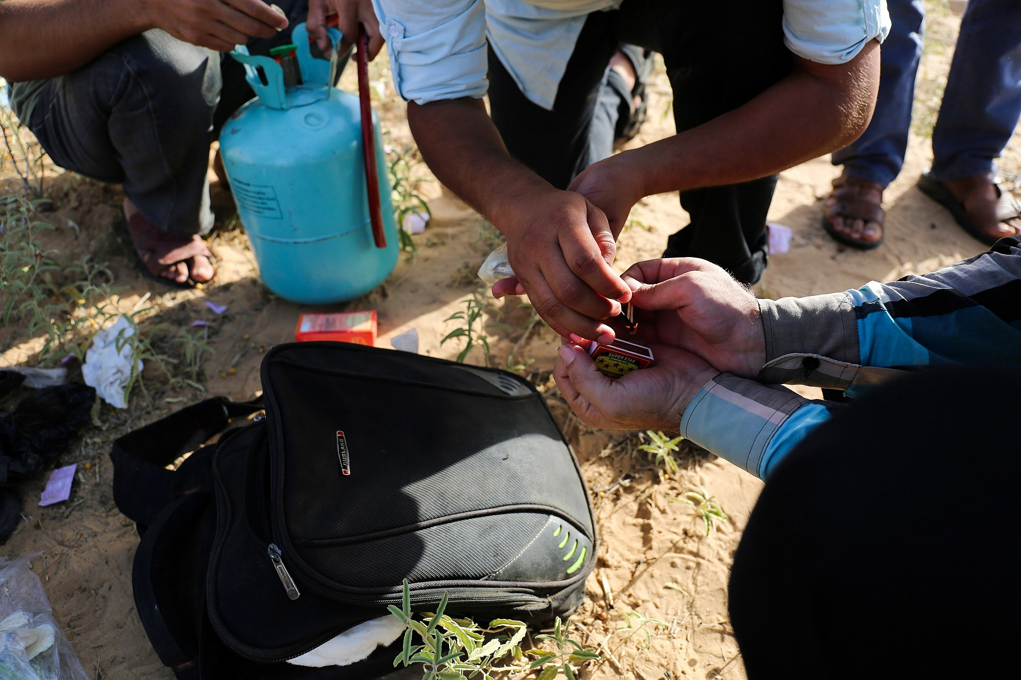 Palestinians prepare to fill a latex condom with helium, to which they will  attach flammable materials to be flown toward Israel near the Gaza border  east ...