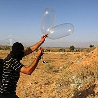 A Palestinian prepares a balloon that will be attached to flammable materials and then flown toward Israel near the Israeli-Gazan border, in Rafah in the southern Gaza Strip June 17, 2018. (Abed Rahim Khatib/Flash90)