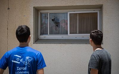 Israelis at a kibbutz near Gaza inspect the scene where a rocket fired from the Strip fell near houses, smashing windows, on June 20, 2018. (Yonatan Sindel/Flash90)
