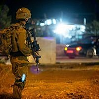 Israeli soldiers stand near the scene of a suspected car-ramming attack at the entrance to the village of Husan, in the West Bank, on June 23, 2018. (Flash90)