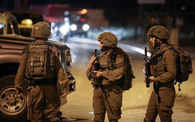 Israeli soldiers stand near the scene of a suspected car-ramming attack at the entrance to the Palestinian village og Husan, in the West Bank, on June 23, 2018.  (Nati Shohat/Flash90)