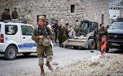 Israeli soldiers at the scene of an attempted ramming attack in the West Bank city of Hebron on June 2, 2018. (Wisam Hashlamoun/Flash90)