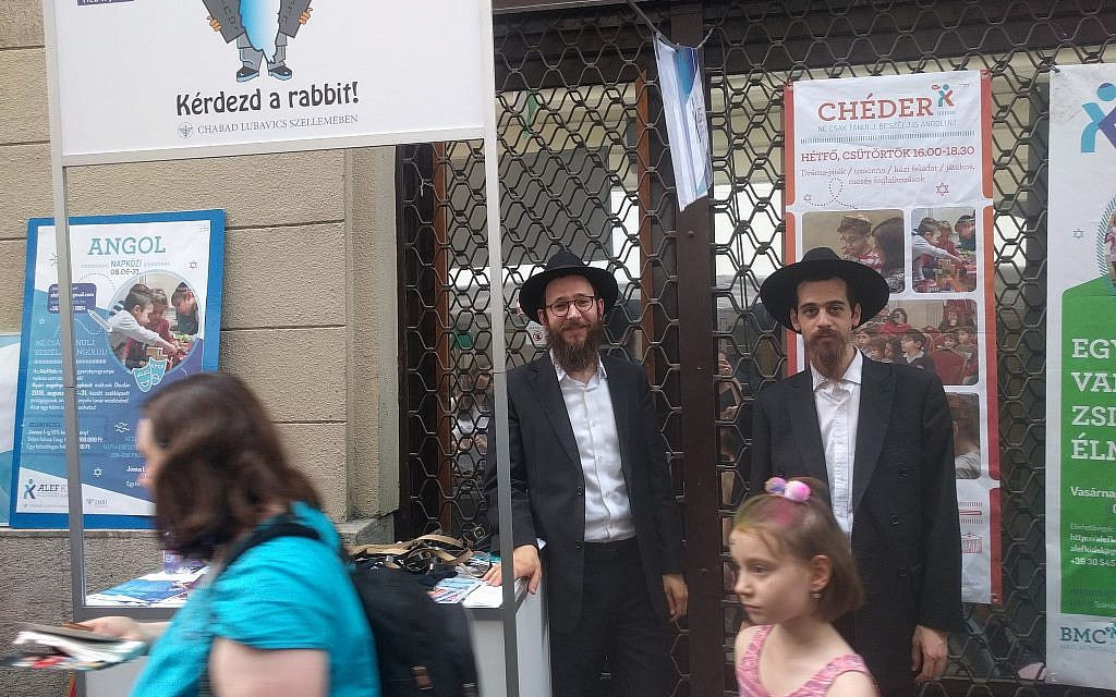 Chabad representatives Rabbis Yitzchak Stell, left, and Chaim Shaul Glitzinstein, offer a chance for passerby to pray and put on phylacteries at the Judafest street festival in Budapest, June 10, 2018. (Yaakov Schwartz/ Times of Israel)