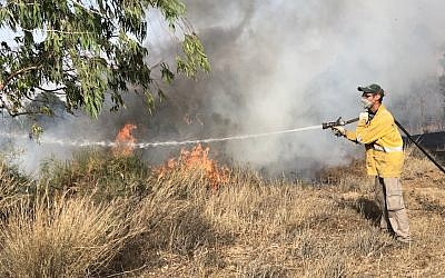 A firefighter extinguishing a blaze on the Israeli border with Gaza, June 11, 2018. (Sam Sokol)