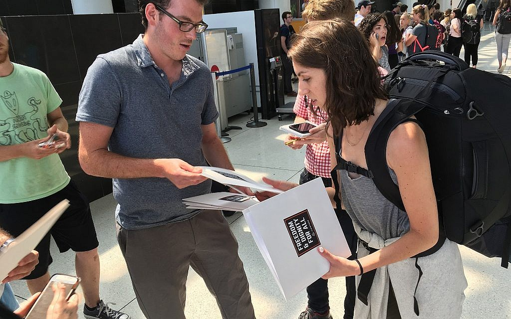 An IfNotNow member distributes materials to a Birthright participant in New York's JFK airport, Monday, June 18, 2018. (Steven Davidson/ Times of Israel)