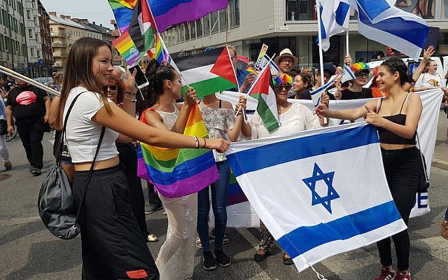 Ilana Edner, marching behind the Israeli flag, with participants of the Jewish contingent of the gay pride parade in Malmo, Sweden, June 10, 2018. (Cnaan Liphshiz)