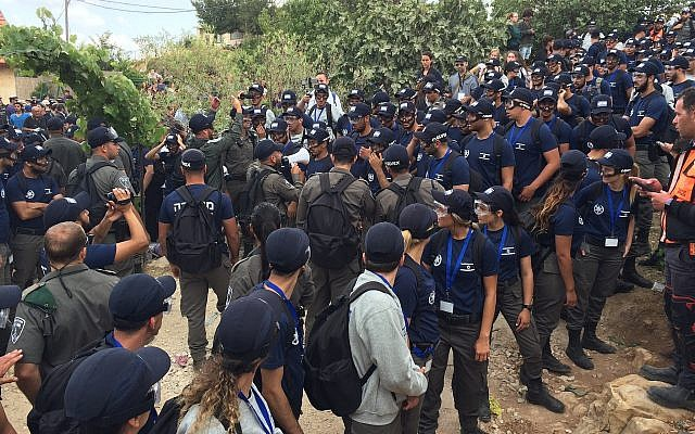 Police and Border Police officers at the Netiv Ha'avot outpost in the Gush Etzion area of the West Bank during the demolition of 15 illegally-built homes, on June 12, 2018. (Luke Tress/Times of Israel)