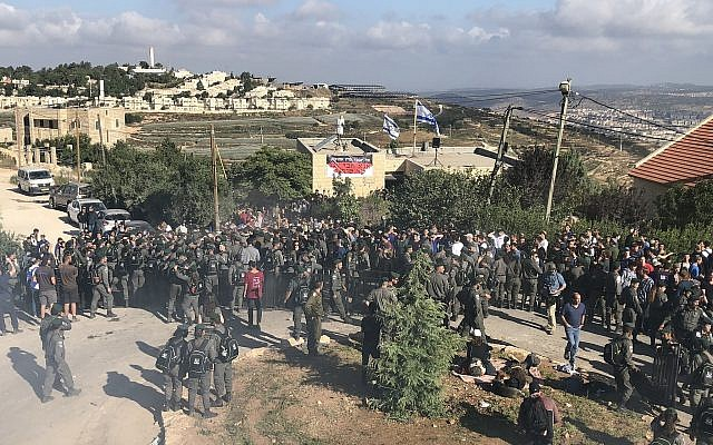 Border Police and protesters at the Netiv Ha'avot outpost in the Gush Etzion area of the West Bank shortly before the expected demolition of 15 homes built illegally on private Palestinian land, on June 12, 2018. (Jacob Magid/Times of Israel)