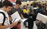 Birthright trip participants read IfNotNow materials distributed in New York's JFK airport on Monday, June 18, 2018. (Steven Davidson/ Times of Israel)
