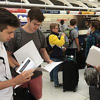 Birthright trip participants read IfNotNow materials distributed as part of a 'send-off' at New York's JFK airport on Monday, June 18, 2018. (Steven Davidson/ Times of Israel)