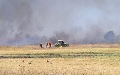 A farmer responds to a fire that broke out in his field outside Kibbutz Mefalsim in southern Israel, which was sparked by an incendiary kite from the Gaza Strip, on June 11, 2018. (Gali Kochba/Kibbutz Movement)