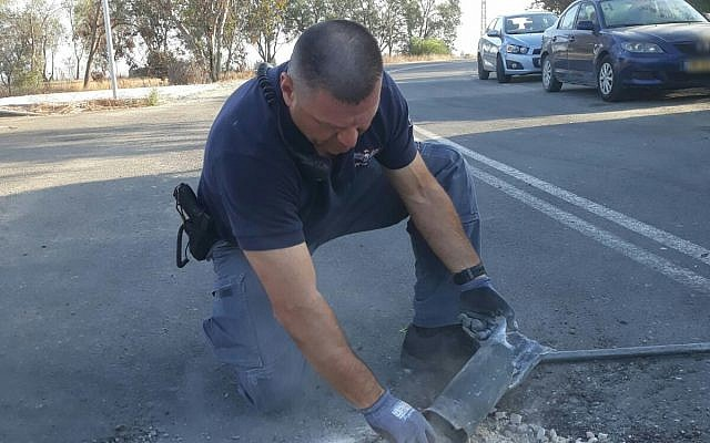 A police sapper handles a rocket fired from Gaza that landed in a street in one of the communities of the Eshkol region on June 20, 2018. (Israel Police)