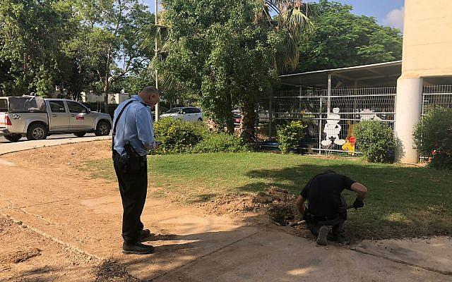 A police sapper digs up a rocket fired from Gaza that landed outside a kindergarten in one of the communities of the Eshkol region on June 20, 2018. (Eshkol region)