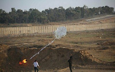 Two Palestinians help fly a 'fire kite' from the Gaza Strip into Israeli territory during mass demonstrations along the security fence on June 8, 2018. (Israel Defense Forces)