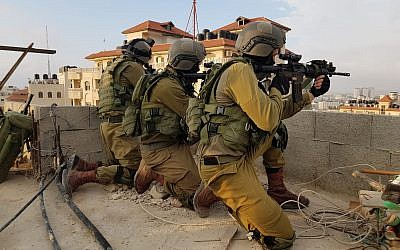 Israeli troops on June 6, 2018, arrest a Palestinian man suspected of killing an IDF soldier by dropping a stone slab on his head in the al-Am'ari refugee camp in Ramallah the month before. (Israel Defense Forces)
