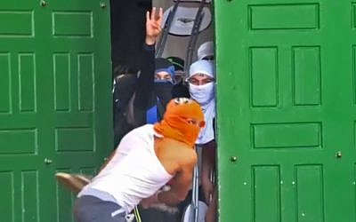 Palestinians throw chairs and other objects from inside the Al-Aqsa Mosque on Jerusalem's Temple Mount, June 7, 2018. (Screenshot from police footage)