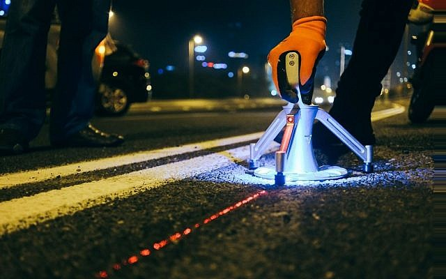 On the Ayalon Highway, workers lay out smart studs developed by Israeli startup Valerann (Courtesy)