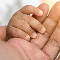 Illustrative image of a baby holding hands (boonchai wedmakawand; iStock by Getty Images)