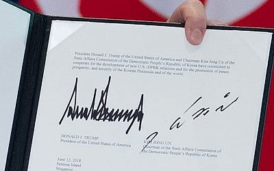 The signatures of US President Donald Trump (L) and North Korea's leader Kim Jong Un (R) are seen on a document held up by Trump following a signing ceremony during their historic US-North Korea summit, at the Capella Hotel on Sentosa island in Singapore, on June 12, 2018. ( AFP PHOTO / SAUL LOEB)
