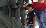 A boy from Honduras is shown being taken into custody by US Border Patrol agents near the US-Mexico Border near Mission, Texas, on June 12, 2018. (John Moore/Getty Images via JTA)