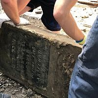 Volunteers rescue a Jewish headstone used to pave a street in the western Ukraine city Lviv, one of up to 100 headstones discovered during roadwork in the center of the city in June 2018. (Marla Raucher Osborn, Rohatyn Jewish Heritage/via JTA)