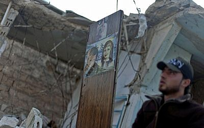 In this November 16, 2012, file photo, a Free Syrian Army fighter stands next to a painting on a piece of wood left in a destroyed house in the town of Taftanaz, on the outskirts of Idlib, Syria. (AP Photo/Khalil Hamra, File)