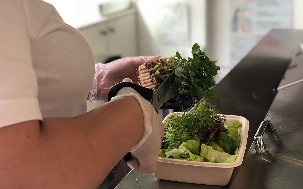 Liz Vaknin cuts microgreen with a pair of scissors at her restaurant Harvest2Order in New York City. (Courtesy)