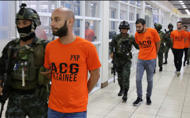 In this photo provided by the Philippine National Police, SAF (Special Action Force) members escort Israeli nationals following a raid at Clark Freeport Zone, Pampanga province, June 7, 2018, in Quezon city, northeast of Manila, Philippines. Police say they have arrested nearly 500 people, including eight Israeli nationals, who they say are involved in an online financial fraud that victimized people overseas, including in Australia and South Africa. (Philippine National Police via AP)