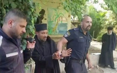 Screenshot from Channel 10 News shows police officers removing a handcuffed Ethiopian monk from an Ethiopian Church-owned property in Jerusalem, on May 31, 2018,