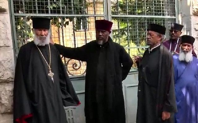 Ethiopian monks gather outside an Ethiopian Church owned complex from which police evicted them on May 31, 2018. The eldest, aged 84, stands on the left. (Channel 10 News screenshot)