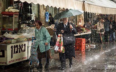 Israelis walking in a downpour rain while shopping at the Mahane Yehuda market in Jerusalem, April 9, 2018. (Liba Farkash/Flash90)