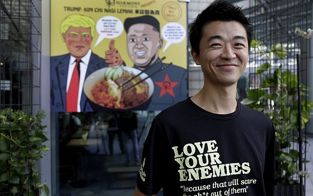 """Zach Wen, 34, co-founder of Harmony Nasi Lemak, poses in front of an advertisement  showing cartoon caricatures of US President Donald Trump and North Korean leader Kim Jong Un, supposedly the inspiration behind a local dish, the """"Trump-Kim Chi Nasi Lemak,"""" in Singapore, on June 7, 2018. (AP Photo/Wong Maye-E)"""