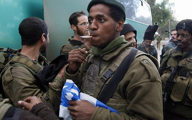 An Israeli soldier holds a national flag as he smokes a cigarette near the Israel-Gaza border after his infantry unit left the Gaza Strip on January 18, 2009. (Menahem Kahana/AFP/Getty Images/via JTA)