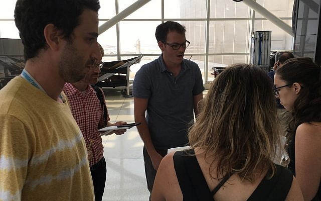 A Birthright trip leader discourages trip participants from speaking to IfNotNow representatives at New York's JFK airport, Monday, June 18, 2018. (Steven Davidson/ Times of Israel)