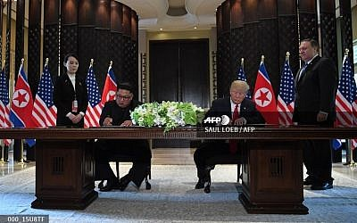 US President Donald Trump (2nd R) and North Korea's leader Kim Jong Un (2nd L) sign documents as US Secretary of State Mike Pompeo (R) and the North Korean leader's sister Kim Yo Jong (L) look on at a signing ceremony during the US-North Korea summit at the Capella Hotel on Sentosa island in Singapore on June 12, 2018. (Saul Loeb/AFP)