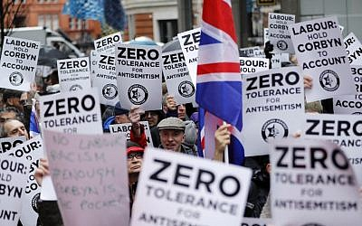 Illustrative: People hold up placards and Union flags as they gather for a demonstration organized by the Campaign Against Anti-Semitism outside the head office of the British opposition Labour Party in central London on April 8, 2018. (AFP/Tolga Akmen)