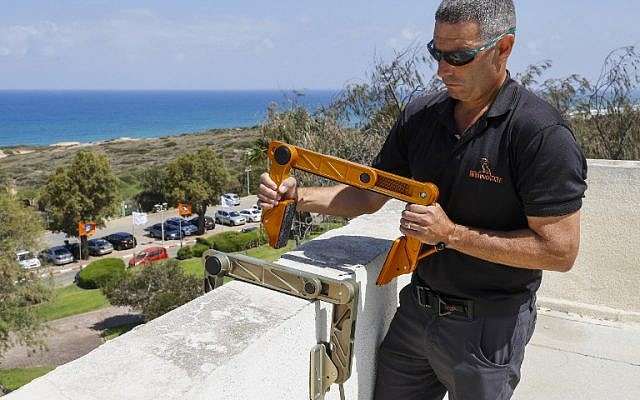 """Idan Peretz, a former member of the Israeli army special forces and co-founder of the tactical solutions start-up Highnovate, holds up his """"Roof Access Fast Anchor"""" (RAFA) tool during a demonstration at the Wingate Institute near Netanya in central Israel on June 11, 2018 (AFP PHOTO / JACK GUEZ)"""