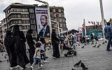 """Pedestrians walk past a poster of Turkish President Recep Tayyip Erdogan under the caption, """"Thank you Istanbul,"""" at Taksim Square in Istanbul on June 28, 2018. (AFP Photo/Bulent Kilic)"""