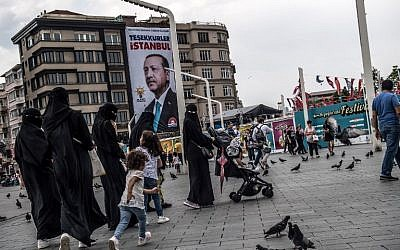"Pedestrians walk past a poster of Turkish President Recep Tayyip Erdogan under the caption, ""Thank you Istanbul,"" at Taksim Square in Istanbul on June 28, 2018. (AFP Photo/Bulent Kilic)"