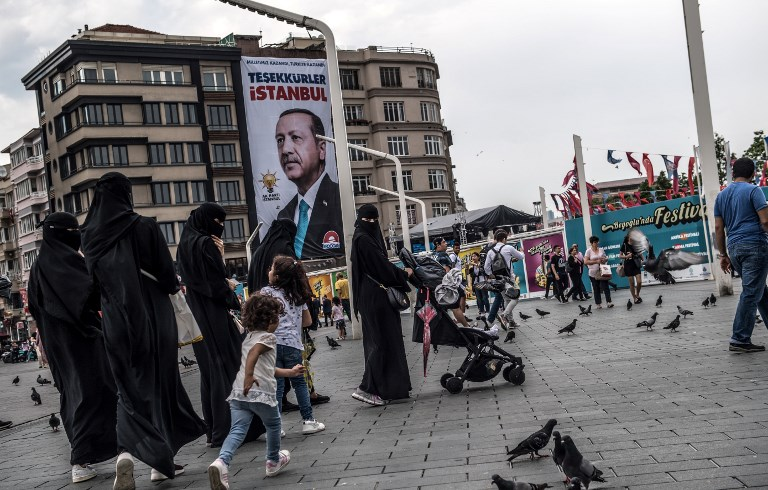 Pedestrians walk past a poster of Turkish President Recep Tayyip Erdogan under the caption