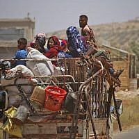 Syrians displaced by government forces' bombardment in the southern Daraa province countryside drive near the town of Shayyah, south of the city of Daraa, towards the demilitarized zone separating the Israeli and Syrian Golan heights on June 29, 2018. (AFP Photo/Mohamad Abazeed)
